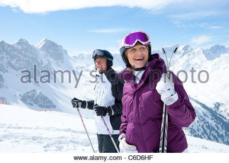 Smiling senior couple with skis on snowy mountain - Stock Photo