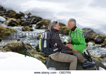 Smiling couple with backpack sitting on rock and drinking coffee near stream in snow - Stock Photo