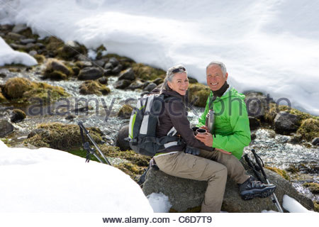 Portrait of smiling couple with backpack drinking coffee and sitting on rock near stream in snow - Stock Photo