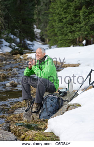 Smiling man with backpack and ski poles sitting at edge of stream in snowy woods - Stock Photo