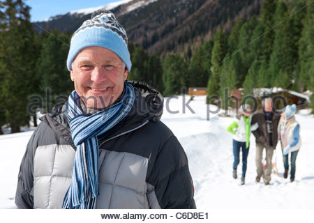Portrait of smiling senior man in snowy woods with friends in background - Stock Photo