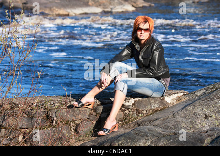 Young redheaded woman is sitting on the rock near by river on sunshine - Stock Photo
