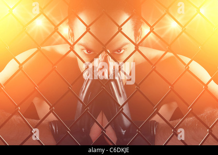 Cage fighter concentrating , staring at the camera , dramatic lighting - Stock Photo