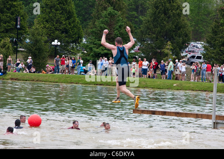 A Tough Mudder participant leaps into the water as part of the 'Walk the Plank' section of the course. Tough Mudder - Stock Photo