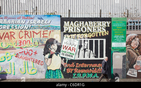Man walking past political posters on Falls Road, Belfast, Northern Ireland - Stock Photo