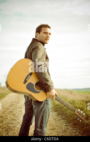 Man with a guitar walking along a road - Stock Photo