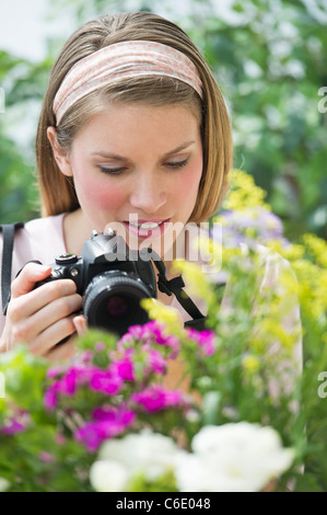 USA, New Jersey, Jersey City, Young woman photographing flowers - Stock Photo