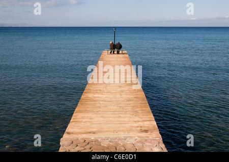 A couple on a jetty, Molivos, Greece - Stock Photo