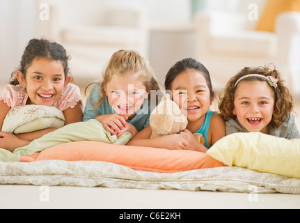 USA, New Jersey, Jersey City, portrait of girls relaxing on pillows - Stock Photo