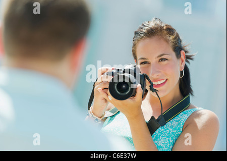 USA, New Jersey, Jersey City, Portrait of young woman taking pictures with camera - Stock Photo