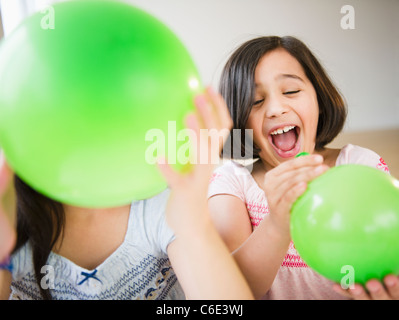 USA, New Jersey, Jersey City, Close up of two girl's playing with green balloons - Stock Photo