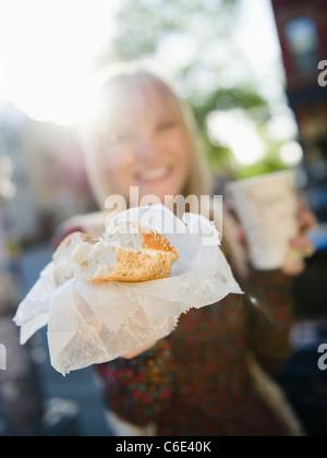 USA, Brooklyn, Williamsburg, Woman showing bagel - Stock Photo