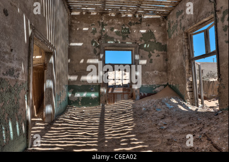 Light pentrates through the old floorboards casting shadows on the walls, Engineers House in Kolmanskop near Luderitz, - Stock Photo