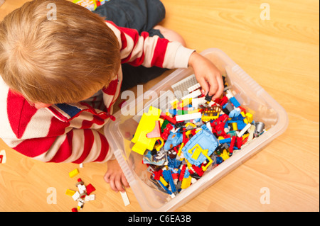 A seven year old boy playing Lego indoors in the Uk - Stock Photo