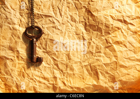 Blank sheet of crumpled paper and old key on chain - Stock Photo