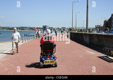 Senior man using a mobility scooter on the seafront promenade. Morecambe, Lancashire, England, UK, Britain - Stock Photo