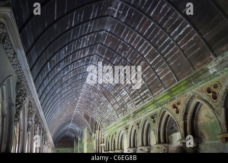 Corridor in cloister at Mont Saint Michel monastery with wooden rib vaulted ceiling and stone arched walls. - Stock Photo