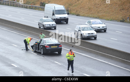 HIGHWAYS AGENCY TRAFFIC OFFICERS  ATTENDS TO A  STRANDED MOTORIST  IN THE FAST LANE OF THE M6 MOTORWAY  FOLLOWING - Stock Photo