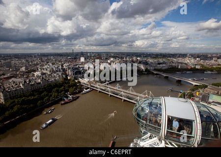 The London Eye with one of it's pods full of tourists overlooking the River Thames and Charing Cross Station. - Stock Photo