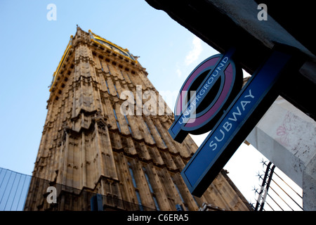 Westminster Underground Station sign next to Big Ben and the Houses of Parliament, London United Kingdom. - Stock Photo