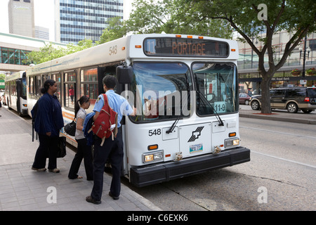 passengers boarding winnipeg transit bus at bus stop on portage ave manitoba canada - Stock Photo