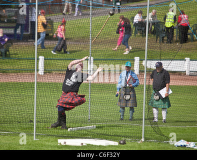 Competitor throwing the hammer, Scottish standing style, in the Heavy Events at the Cowal Highland Gathering 2011 - Stock Photo