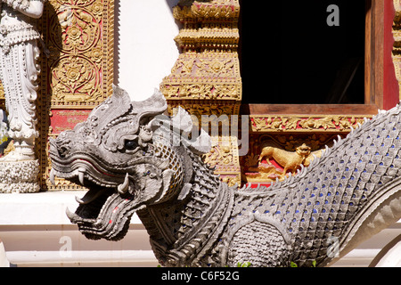 A sculpted dragon with mosaic decoration protects the entrance to a temple in Chiang Mai - Stock Photo