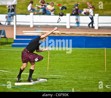 Kilted German athlete throwing a hammer while competing in the Heavy Events at the Cowal Highland Gathering 2011 - Stock Photo