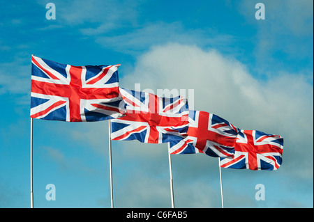 Four Union Jack flags flapping in the wind against a blue sky - Stock Photo