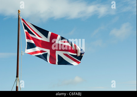 Union Jack flag flapping in the wind against a blue sky - Stock Photo