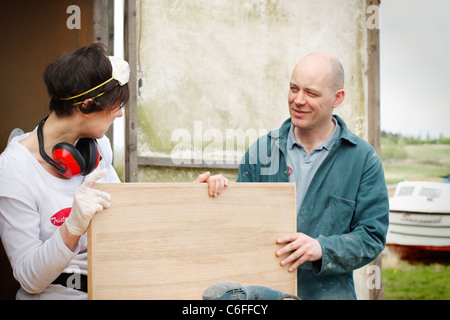 A man and a woman discussing the sanding work of a wooden door, wearing Personal Protective Equipment (PPE) for - Stock Photo