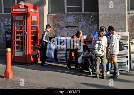 London china town street scene people helping themselves to free Chinese newspaper in Chinatown Gerrard Street London - Stock Photo