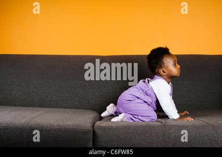 A baby girl on a sofa - Stock Photo