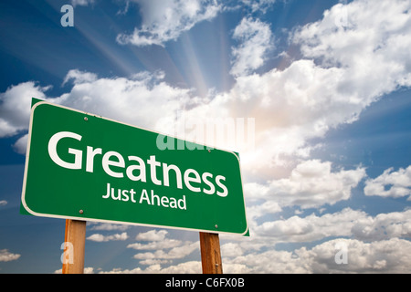 Greatness, Just Ahead Green Road Sign Over Dramatic Sky, Clouds and Sunburst. - Stock Photo