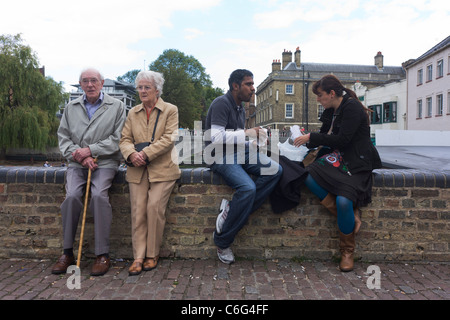 Elderly couple rest on a Cambridge wall as a younger, Asian man and European woman eat food. - Stock Photo