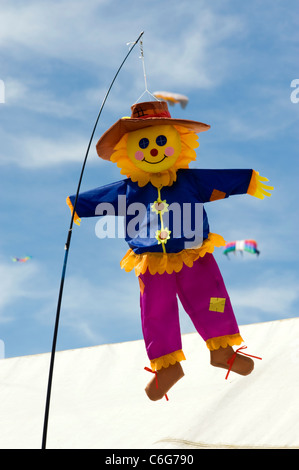 small colourful scarecrow kite flying in the breeze at southsea kite festival - Stock Photo