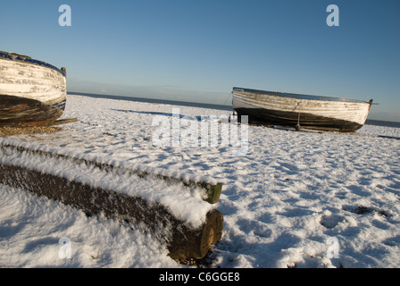 Fishing Boats on Aldeburgh Beach covered in snow. - Stock Photo