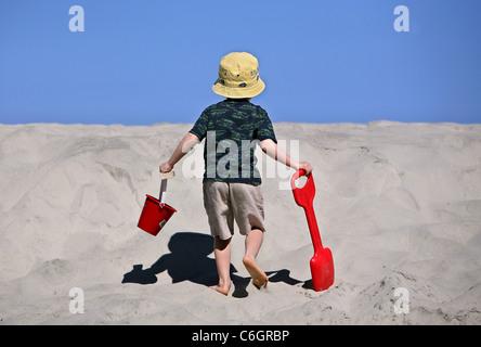 A boy walks up a sand dune on the beach at Folly Beach, South Carolina. - Stock Photo