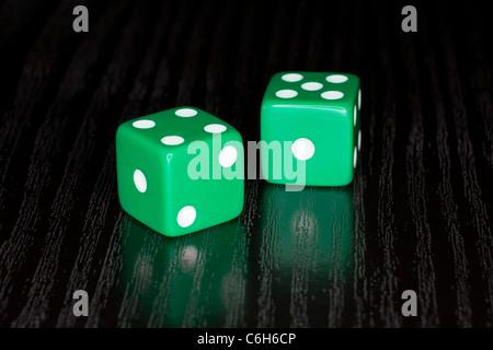 Green Dice on a semi reflective black surface - Stock Photo
