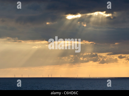 Rays of the late afternoon sun shining through clouds onto an offshore wind farm in Germany - Stock Photo