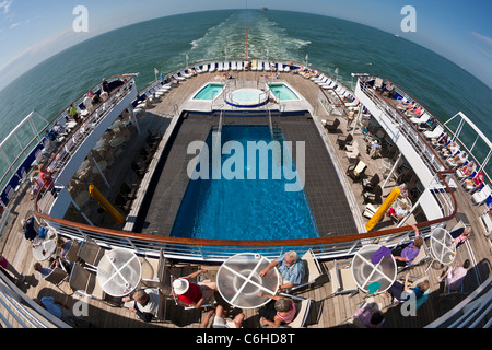 Fisheye view towards the stern across the lido deck of the Fred Olsen cruise ship 'Black Watch' showing the swimming - Stock Photo