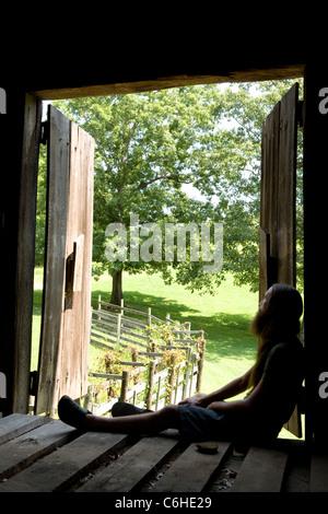 Young Bearded Man looking out barn doors - Cedar Mountain, North Carolina, USA - Stock Photo
