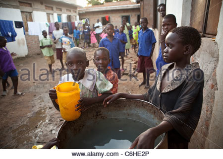 Young girl collecting water from a large drum at an orphanage - Stock Photo