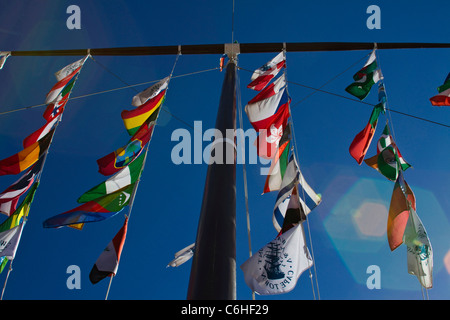Flags on a tall flagpole in the V&A waterfront - Stock Photo