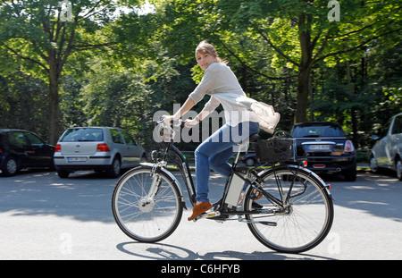 Girl riding on electric bicycle, pedelec, ebike, e-bike, Dortmund, Germany - Stock Photo