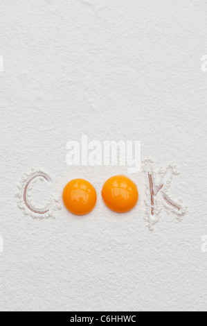 The word Cook written in flour using egg yolks - Stock Photo