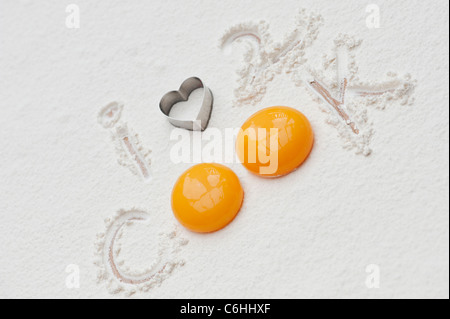 I Love to Cook . Eggs, Flour, and a heart shape biscuit cutter - Stock Photo
