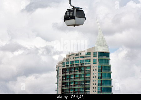 Cable car passing over a tower building, Parque das Naçoes (Park of the Nations), Lisbon, Portugal - Stock Photo