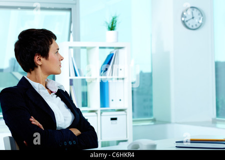 Photo of smart businesswoman sitting in office and looking at clock - Stock Photo