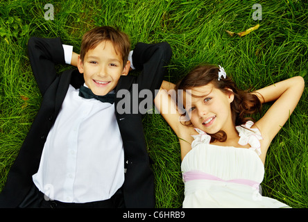 Portrait of smiling children bride and groom lying on green grass and looking at camera - Stock Photo
